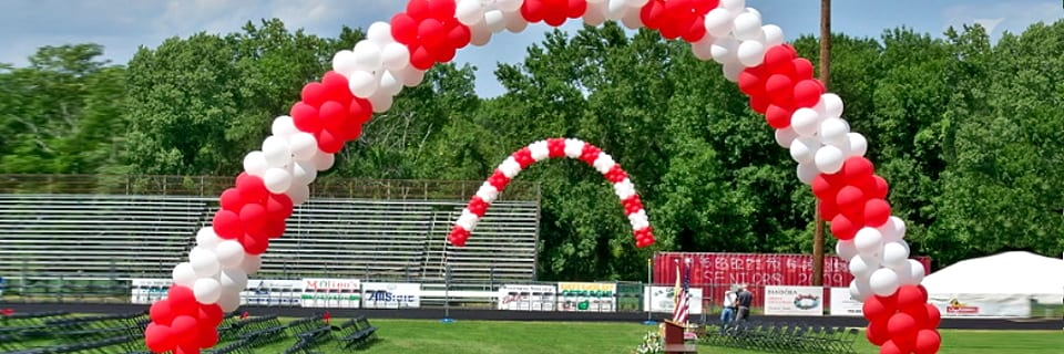 Two large red and white banded packed balloon arches for an outdoor graduation ceremony
